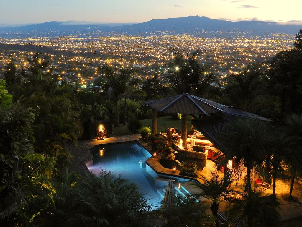 una vista di sera di un resort, si vede la città illuminata e sotto una piccola piscina